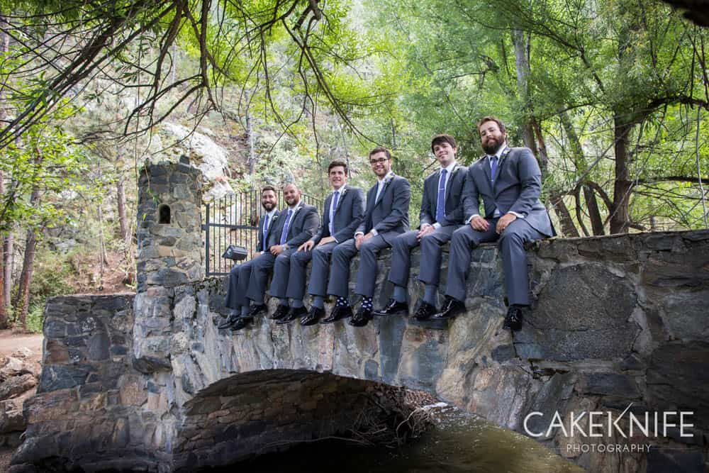 Groomsmen sitting on stone bridge at the Dunafon Castle